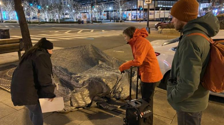 Volunteers stand beside a makeshift tent on a city sidewalk