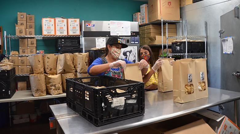 Chavela and Nikki Guerrero bag chips in a commercial kitchen