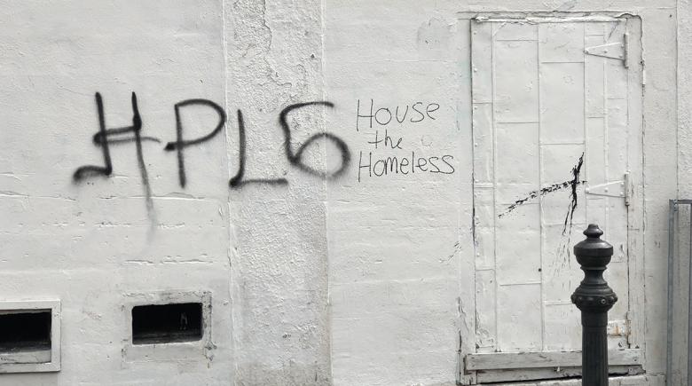 Graffiti on a building reads: House the Homeless