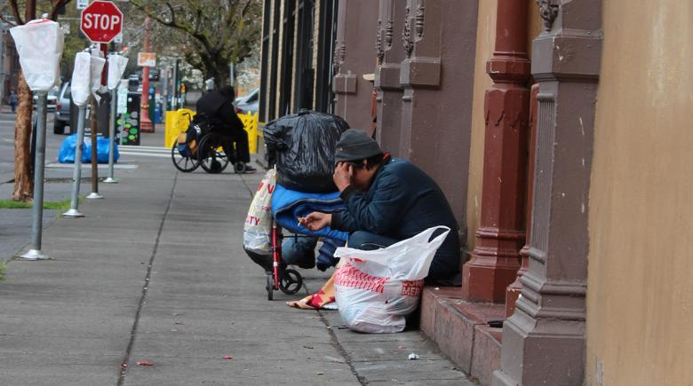 Person on the sidewalk with their possessions