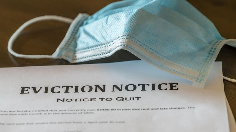 Photo illustration: An eviction notice sits on a table beside a protective mask