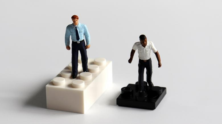 Illustration: Figure of white person on a large white block next to figure of a black person on a small black block