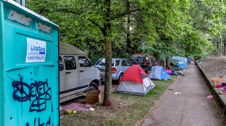 Tents line a sidewalk by Laurelhurst Park in August 2020