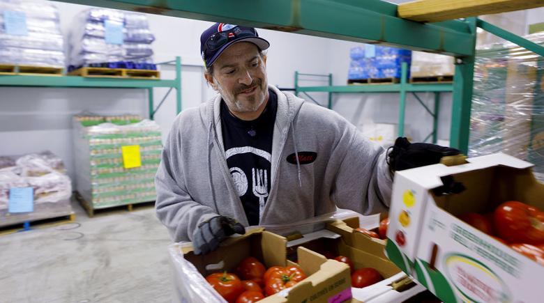 A volunteer sorts through produce