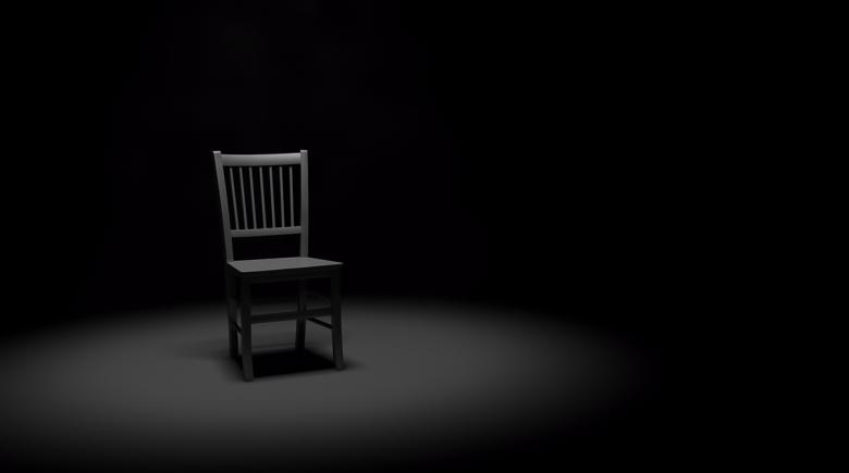 A chair sits empty in a dark room with a spotlight shining on it