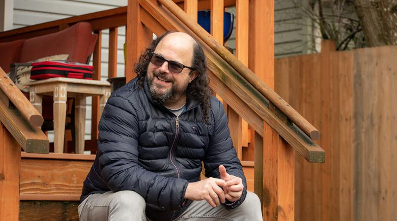 Jeremy Wilson sits on the steps of a porch