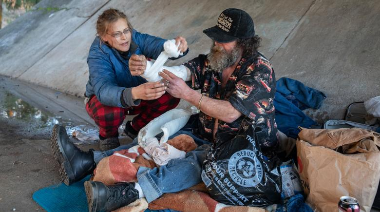 Under an overpass, a camper wraps a bandage around someone's arm