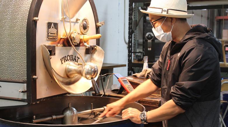Sam Khaute works with a large coffee roasting machine