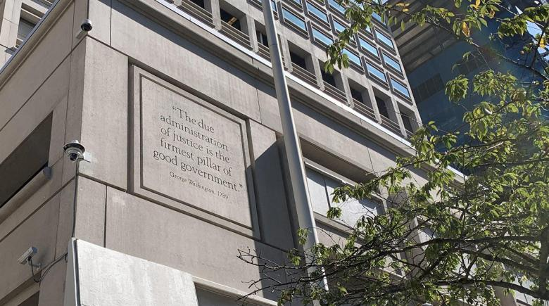 "Cameras are shown on the Justice Center building. A quote on the building reads: ""The due administration of justice is the firmest pillar of good government."""