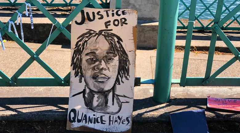 Artwork of Quanice Hayes leans against the rail by the river.