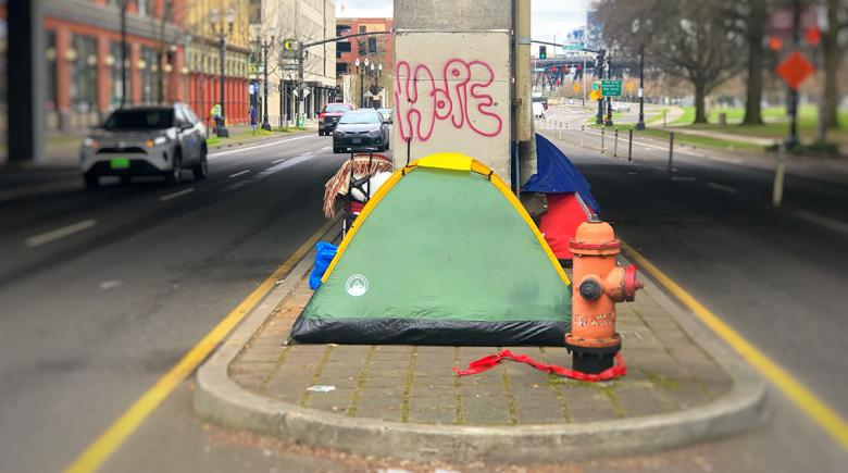 """""""Hope"""" is displayed above a tent"""