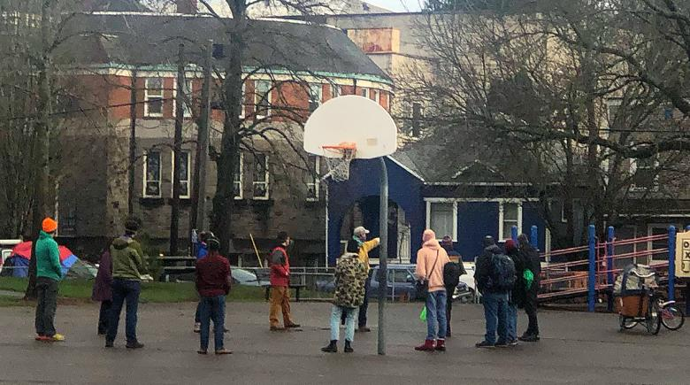 People gather on an outdoor basketball court at Sunnyside Environmental School in Southeast Portland