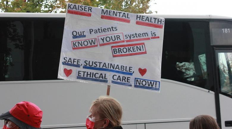 Woman holding a sign that urges Kaiser Permanente to support their employees