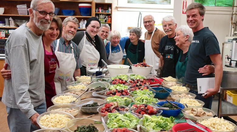 A big meal surrounded by Hard Times Supper volunteers