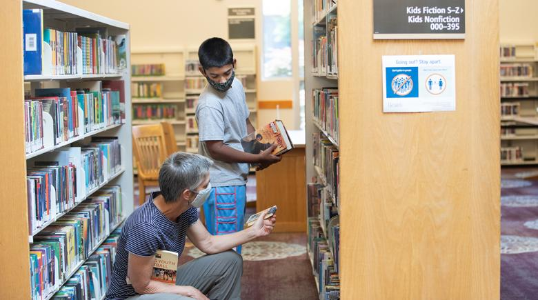 People wear masks while browsing books at the library