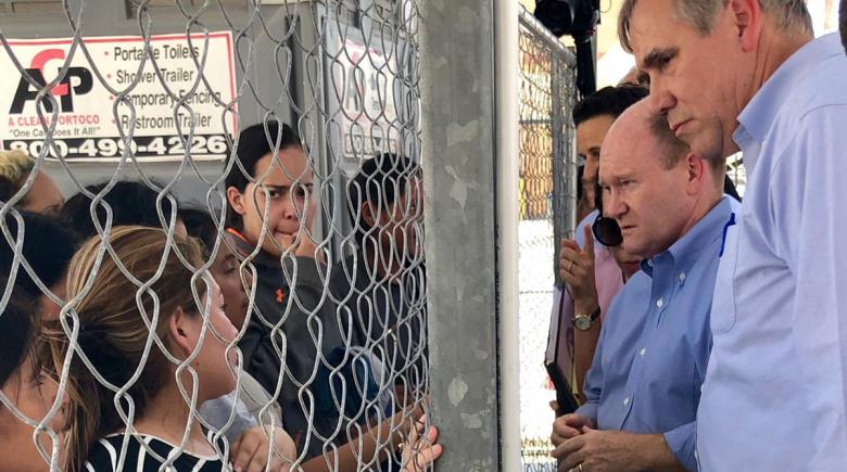 Merkley talks to youths through a chain-link fence