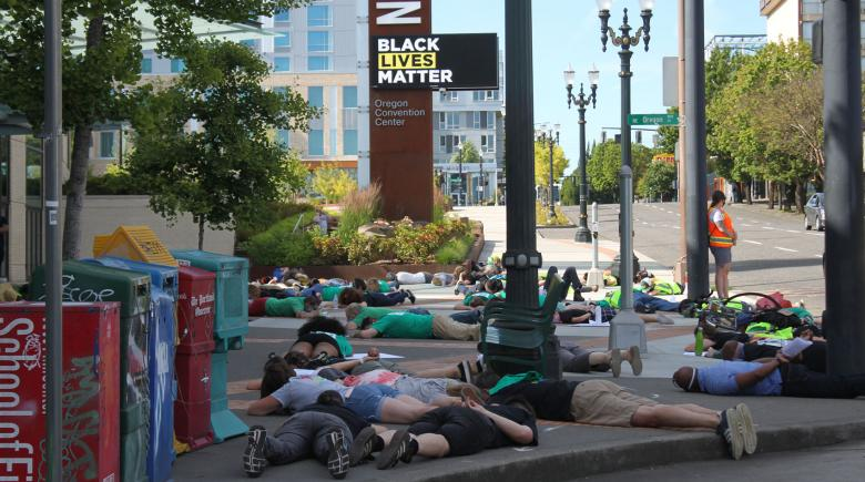 A group of people lies face down on the sidewalk outside the Oregon Convention Center.