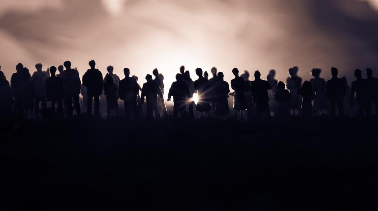 Silhouettes of a crowd standing in front of a foggy background