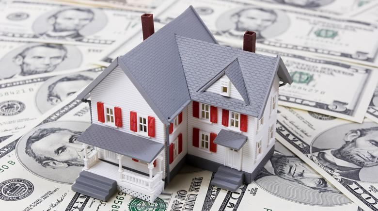 Photo illustration of a house on top of money
