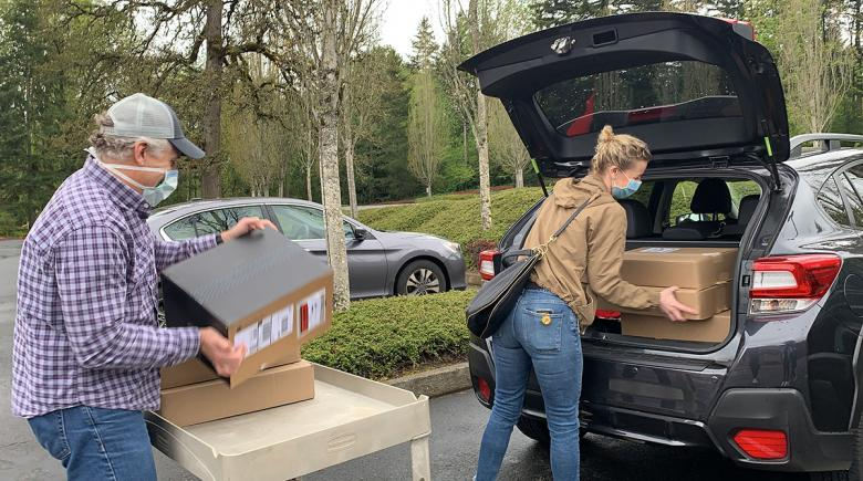 Two people loading a vehicle with boxes