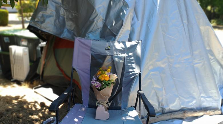 A bouquet of flowers is propped against Dan Newth's tent.