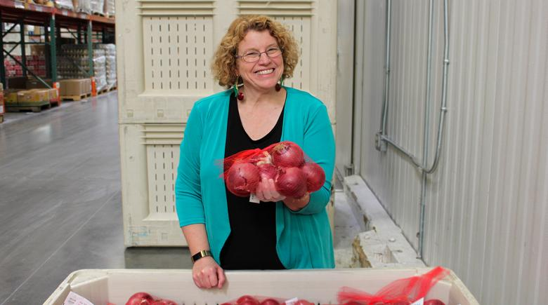 Susannah Morgan holds a bag of fresh onions