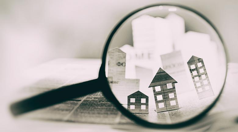 Illustrative photo shows a magnifying glass zooming in on paper houses