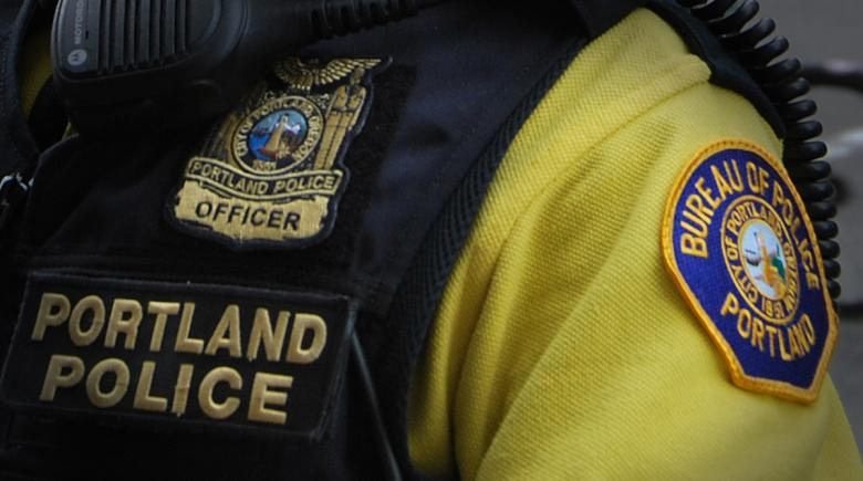 A badge is seen on a Portland police officer's uniform