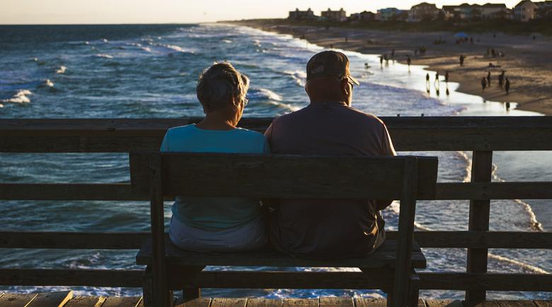 A retirement-age couple sitting on a bench, overlooking the water