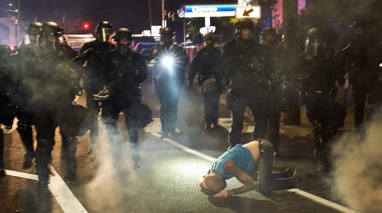 Adam Allen lies on the ground in front of police