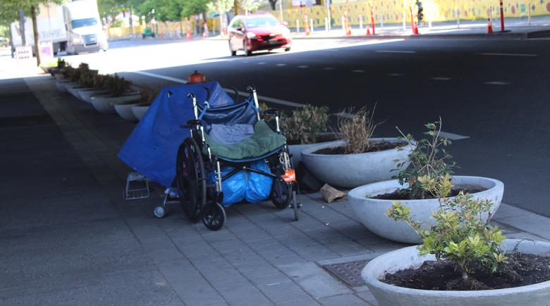 A person's belongings are left next to large planters along Naito Parkway in Portland