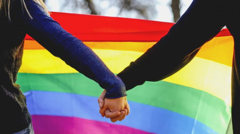 Two people hold hands in front of a rainbow Pride flag
