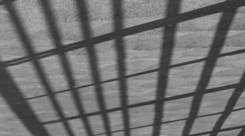 A shadow of prison bars appears on concrete