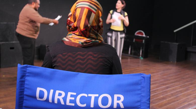 """Aleen sitting in a chair that says """"director"""" on the back"""