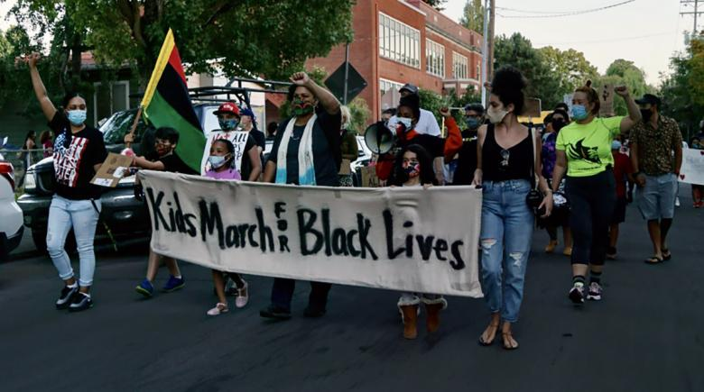 "Kids march with adults, carrying a banner that says ""Kids March For Black Lives"""