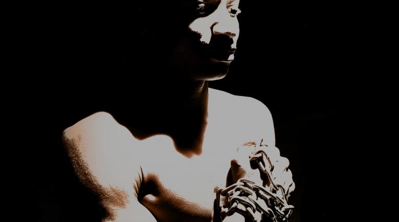 Photo illustration of a Black man whose hands are chained together