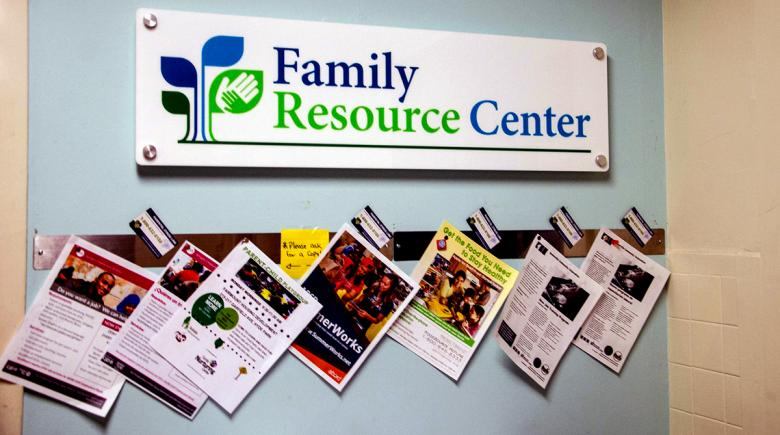A sign on the wall says Family Resource Center, with newspapers displayed beneath it