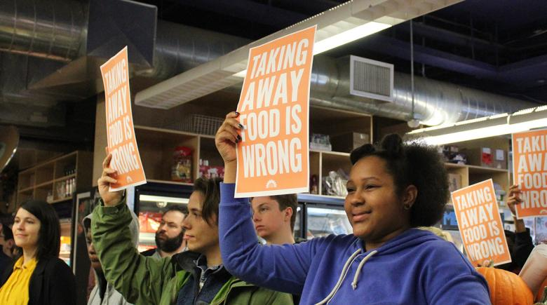 Demonstrators holds signs that say: Taking away food is wrong