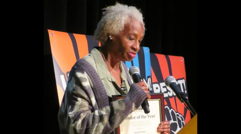 Sandra Hahn at a microphone, holding her award
