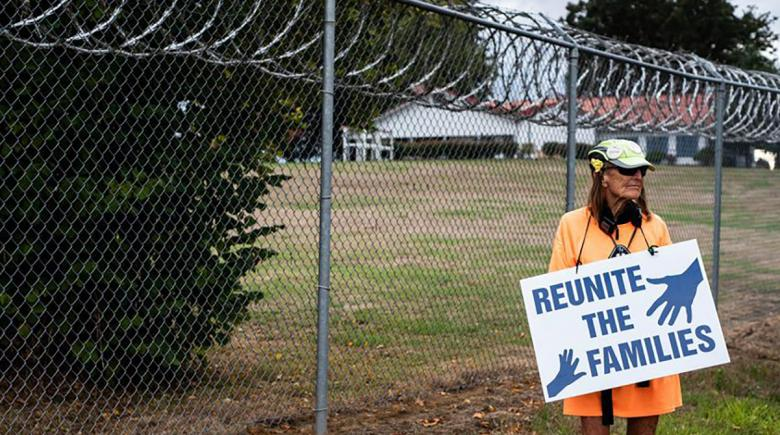 A protester holds a signs that reads: Reunite the Families