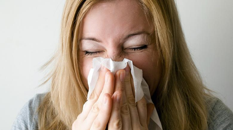 A woman blows her nose
