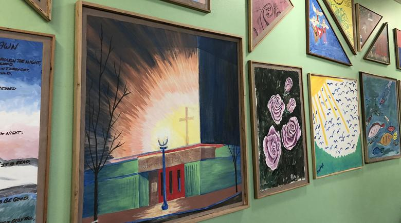 A photo of a wall of paintings, one depicting the red doors in the front of the St. Andre Bessette