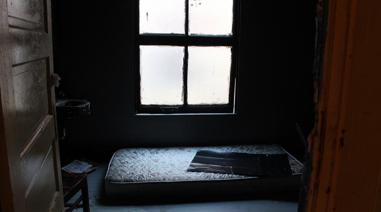 A mattress sits on the floor inside a shabby room