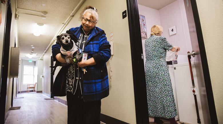 Sharleen walks while another resident does laundry