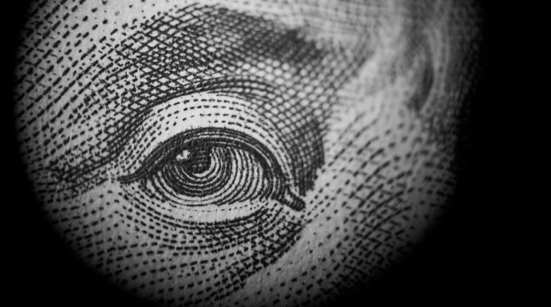 The eye of Benjamin Franklin on a hundred dollar bill