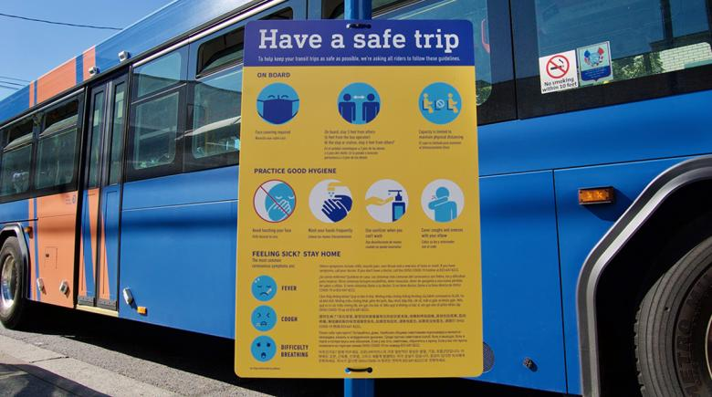 "A ""Have a safe trip"" sign is displayed in front of a TriMet bus"