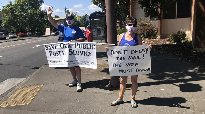 Two people hold signs in support of the Postal Service and against mail delays.