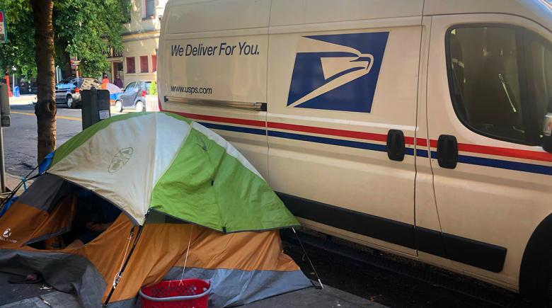 A U.S. Postal Service van is parked beside a tent erected on the sidewalk