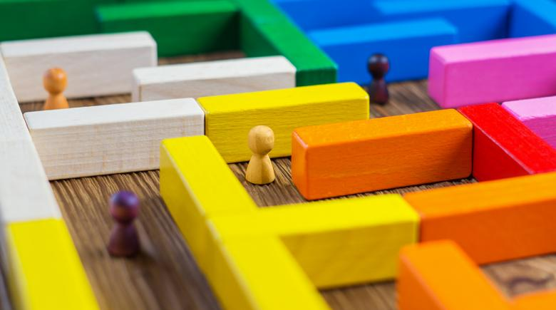 Wood pawns in a maze of toy blocks