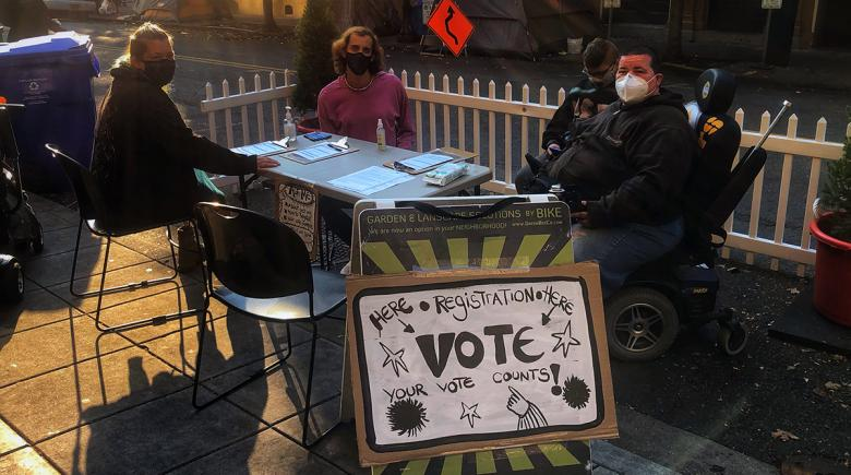 Vendors sit around a table with a voter registration sign in front of it